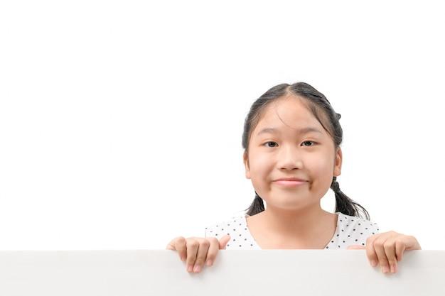 笑顔の女の子は白い背景で隔離の白い看板を保持し、入力テキストのスペースをコピーします