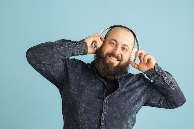 미소. copyspace와 파란색 벽에 고립 된 잘 생긴 백인 남자 초상화. 수염을 가진 세련된 남성 모델. 인간의 감정, 표정, 판매, 광고, 패션, 청소년의 개념.