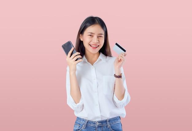 スマートフォンとクレジットカードのオンラインショッピングを保持しているアジアの女性を幸せに笑顔します。