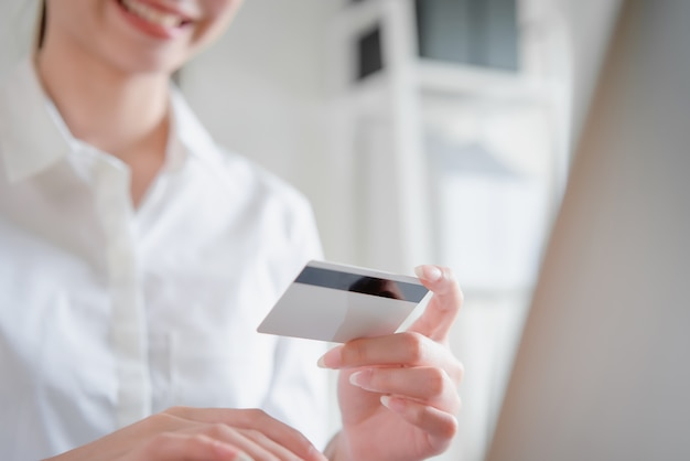 Smile happily asian woman shopping online and holding credit card.
