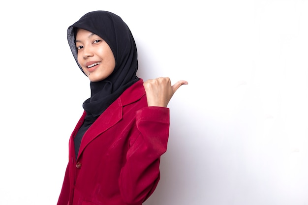 Smile and happy face of asian women with hijab point to present an empty space of content. advertising model concept.