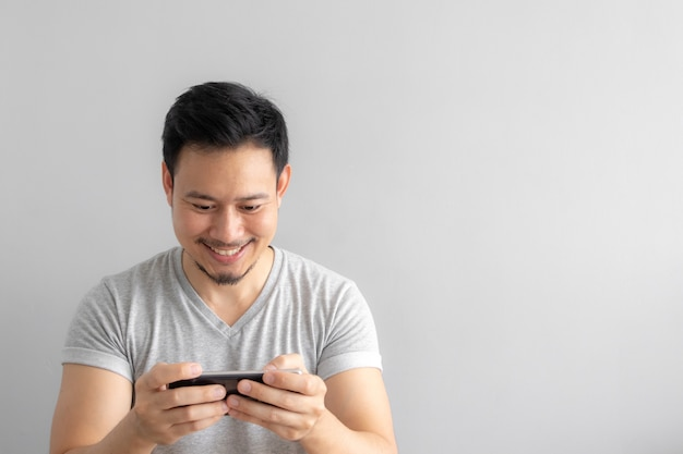 Smile and happy face of man playing mobile game.