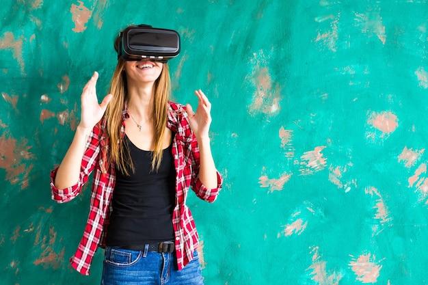 가상 현실의 vr 헤드셋 안경을 사용하여 경험을 얻는 행복한 여자가 손을 많이 움직입니다.