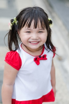Smile is sincere from little girl white shirt and red ribbon.