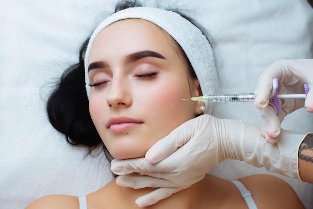 웃는 얼굴 리프팅 및 입술 확대 미용사 의사가 여성의 얼굴에 미용 절차를 수행합니다.