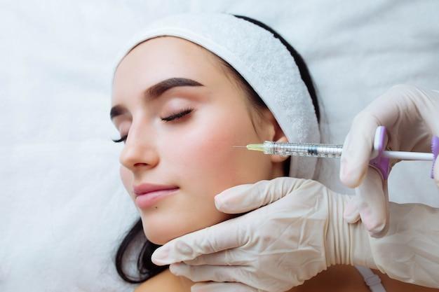 Подтяжка улыбки и увеличение губ косметолог руки врача делают косметическую процедуру для женского лица остроумие