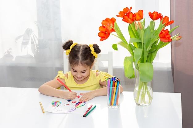 黄色いドレスを着た小さなブルネットの笑顔、赤いチューリップと白いテーブルに座っています