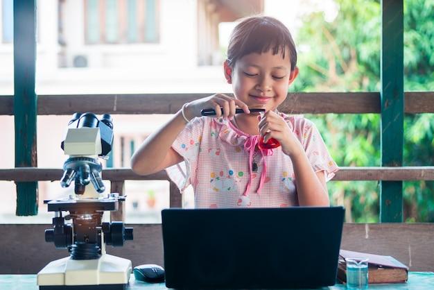 科学の実験を学び、作る小さな子供女の子を笑顔します。ホーム学校教育のコンセプトです。