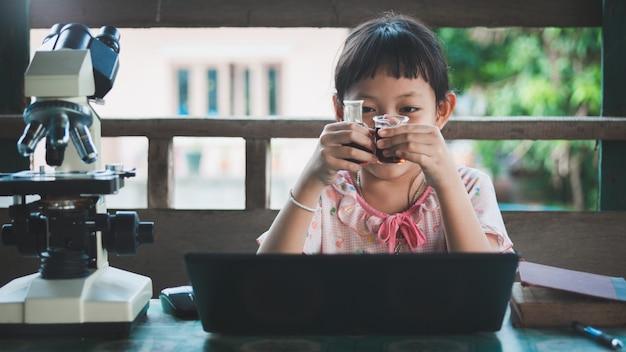 科学実験を学び、作る小さな子供の女の子を笑顔にします。ホームスクール教育の概念。