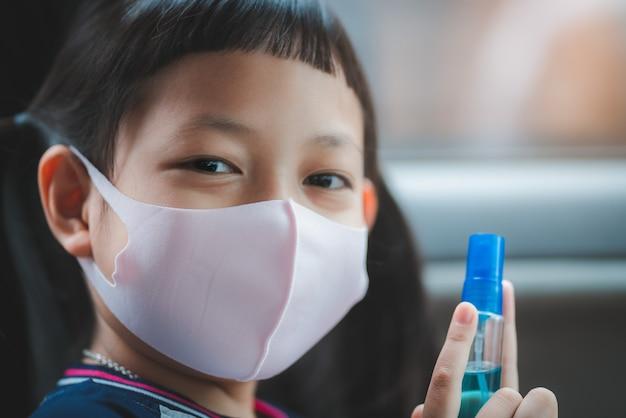 Улыбающаяся маленькая девочка в маске для лица и держит дезинфицирующий спирт для предотвращения заражения руки вирусом и чумной инфекцией covid-19 в ее машине