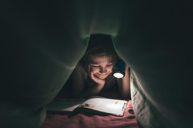 Улыбка маленькой девочки читает книгу под одеялом с фонариком в темной комнате ночью, в постели