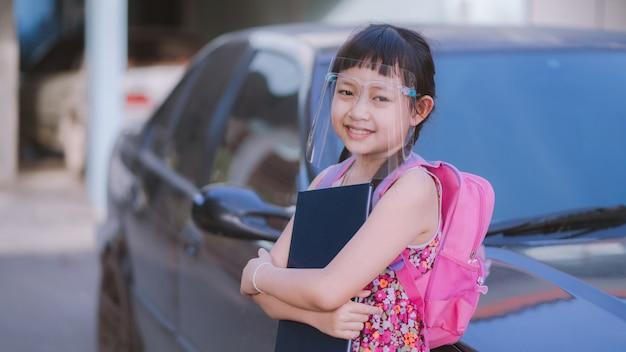 Covid-19 quarantine.16:9のスタイルの後、学校に戻っているときに顔のシールドを身に着けている少女の笑顔