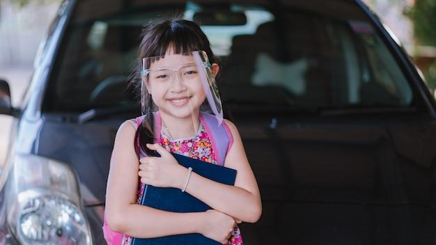 Covid-19 검역 후 학교에 돌아가는 동안 얼굴 방패를 착용하는 작은 소녀 학생 미소 : 16 : 9 스타일