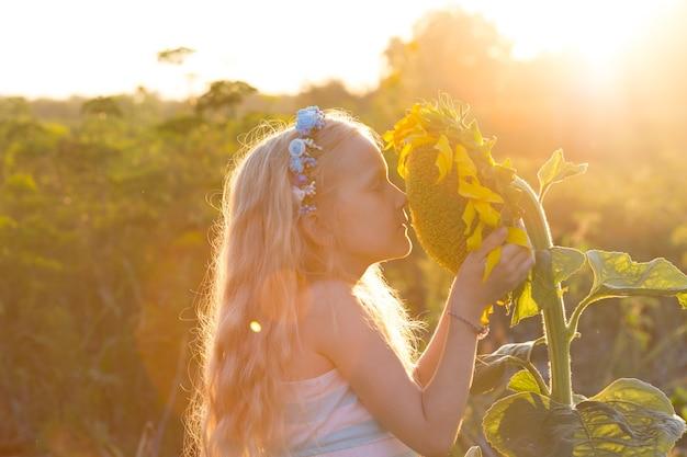 日没時にひまわりと小さな女の子を笑顔