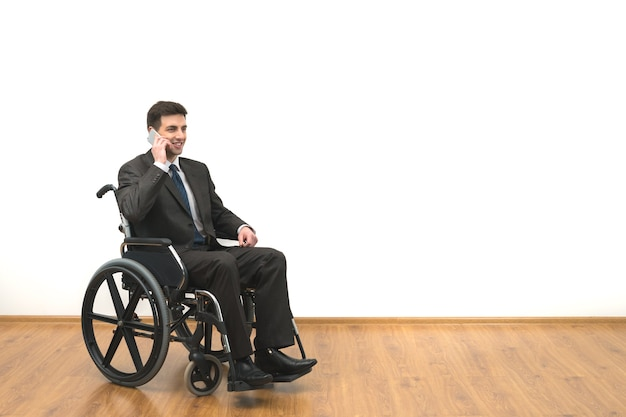 The smile man in the wheelchair phones on the white wall background