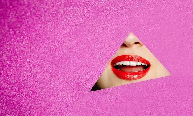 ふっくらした赤い唇を持つ美しい少女の笑顔は、ピンクのきらびやかな紙の穴をのぞきます。ファッションの概念、美容、メイク、化粧品。