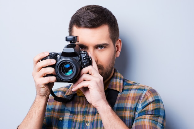 Smile! portrait of confident young man in shirt holding camera in front of his face while standing against grey background
