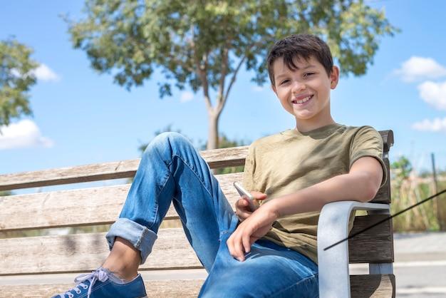Smile schoolboy on bench taking break using mobile