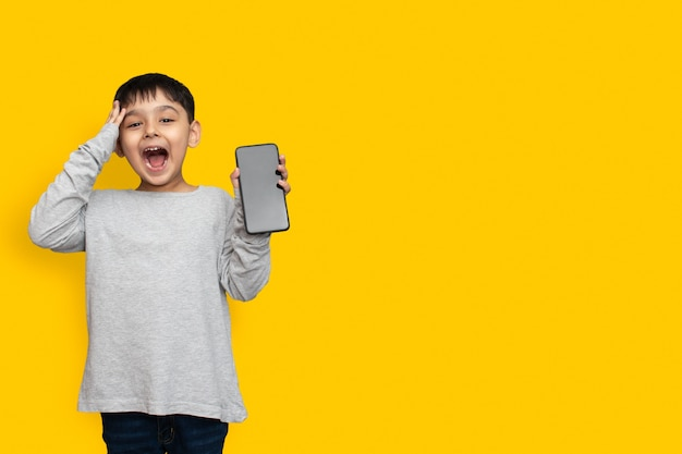 Smile and shocked little boy kid in green grey shirt blank screen of mobile phone on yellow background copy space
