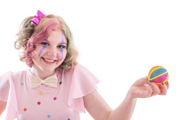 Улыбающаяся девушка-подросток в костюме клоуна с мячом на белом фоне
