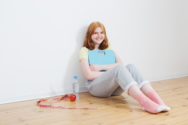 木製の床にスケールを持つ10代の少女を笑顔します。