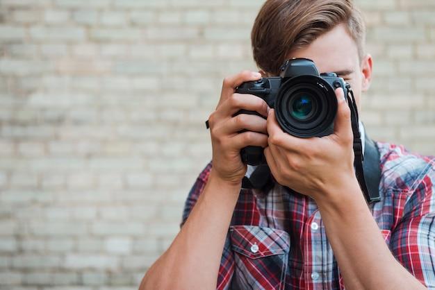 カメラに微笑んでください!レンガの壁に立っている間彼のデジタルカメラであなたに焦点を当てている自信を持って若い男