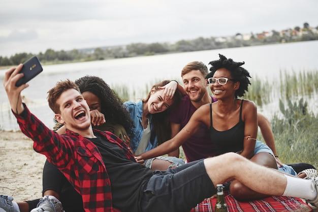 Улыбнись в камеру. группа людей устраивает пикник на пляже. друзья веселятся в выходные.