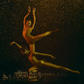 Smile. two young female ballet dancers under water drops and spray. caucasian and asian models dancing together in neon lights. ballet and contemporary choreography concept. creative art photo.
