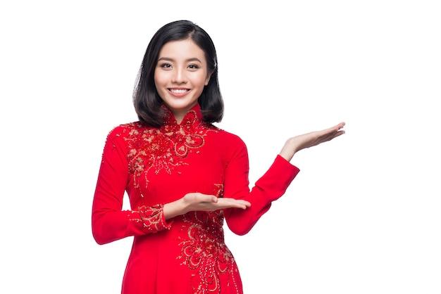 Улыбка вьетнамской женщины в традиционном платье ао дай и представление на белом фоне.