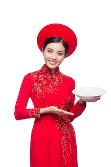 Улыбка вьетнамской женщины в традиционном платье ао дай и представление продукта на белом фоне.