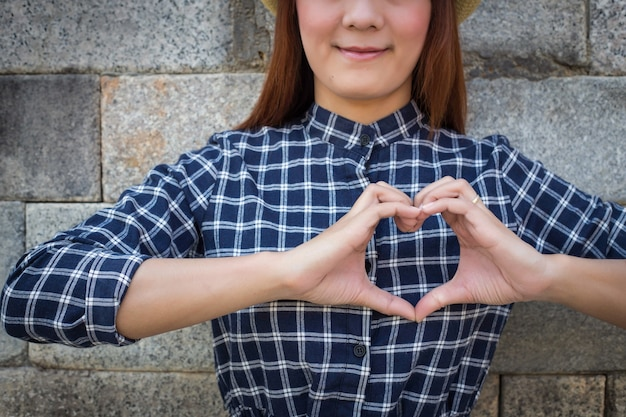 Smile woman holds heart shape on own. love emotion (focus shirt)
