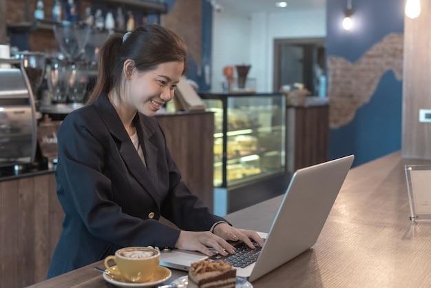 Улыбка женщины, глядя на ноутбук и миллиметровку энергично в кафе
