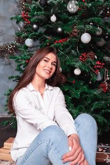 クリスマスツリー、幸せの概念の女性を笑顔します。