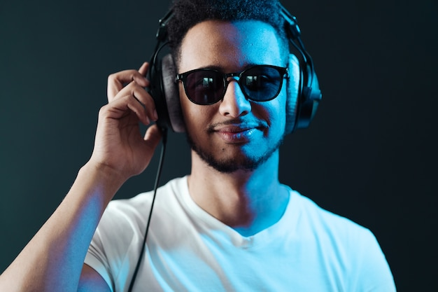 Smile young african american man portrait wearing headphones and enjoy music over black wall