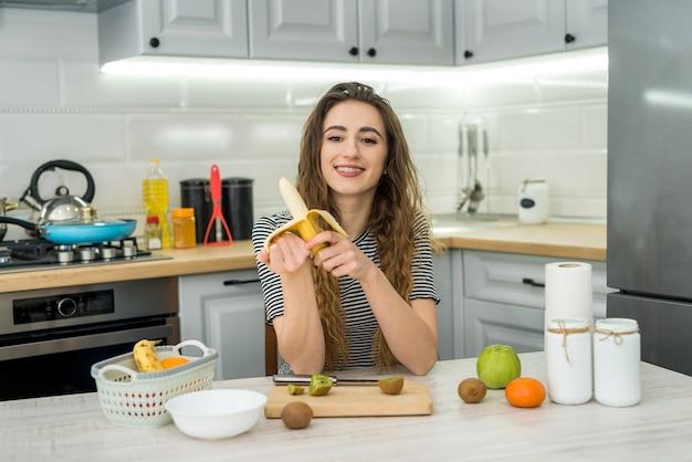 キッチンでフルーツと新鮮なサラダを調理する若い女性の笑顔。健康的な生活様式。ダイエット