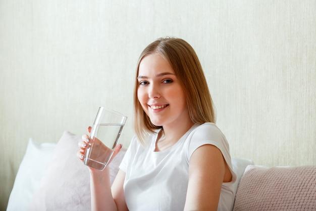Улыбка молодой женщины выпивает стакан чистой воды утром после пробуждения в своей спальне. счастливая девочка-подросток поддерживает водный баланс для здоровья тела, выпивая чистую воду.