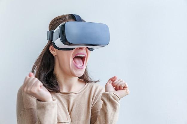 Улыбка молодой женщины носить с помощью виртуальной реальности vr очки шлем гарнитуры на белом фоне.