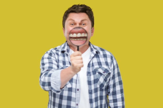 Smile zoom or tooth care concept. portrait of middle aged man in casual checkered shirt standing, holding magnifying glass on his teeth, looking at camera. studio shot, isolated on yellow background.