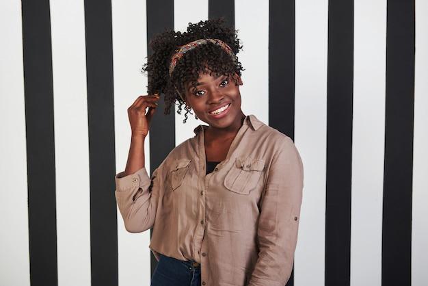 미소 아프리카 계 미국인 여자가 서서 배경에서 세로 흰색과 검은 색 선으로 스튜디오에서 그녀의 머리를 만집니다.