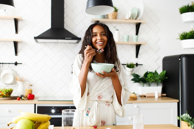 Smiled attractive mulatto woman is eating cutted fruits on white modern kitchen dressed in nightwear with messy loose hair and looking straight