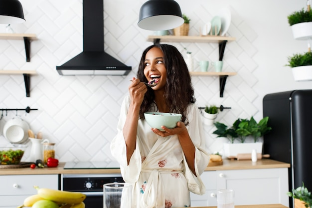 Smiled attractive mulatto woman is eating cutted fruits on white modern kitchen dressed in nightwear with messy loose hair
