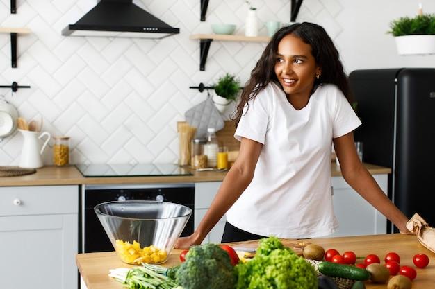 미소 아름다운 혹 백 혼혈 아 여자는 현대 부엌에 신선한 야채 가득 테이블 근처에 서있다