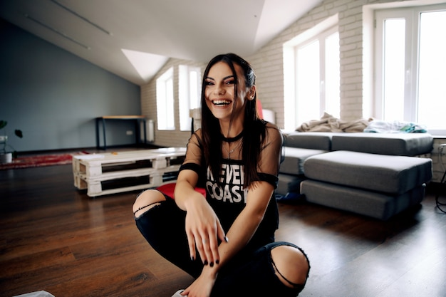 Smiled brunette woman dressed in casual informal clothes is sitting on the floor in the room with black manicure