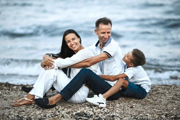 Smiled family is sitting on the rocky beach near the stormy sea and hugging, parents and child