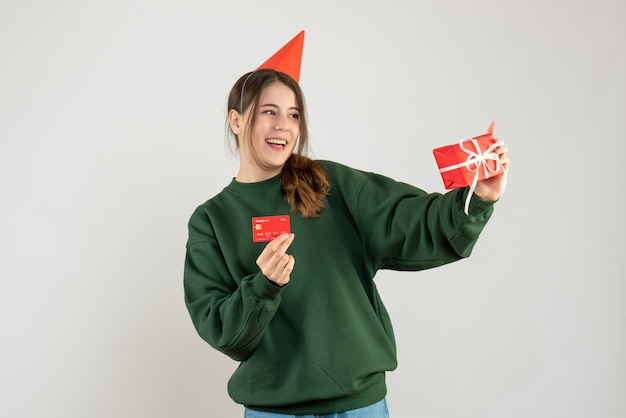 Smiled girl with party cap holding gift and card on white