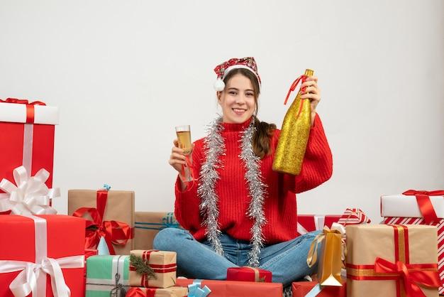 Sorrise ragazza con cappello santa tenendo champagne e vetro seduto intorno presenta su bianco