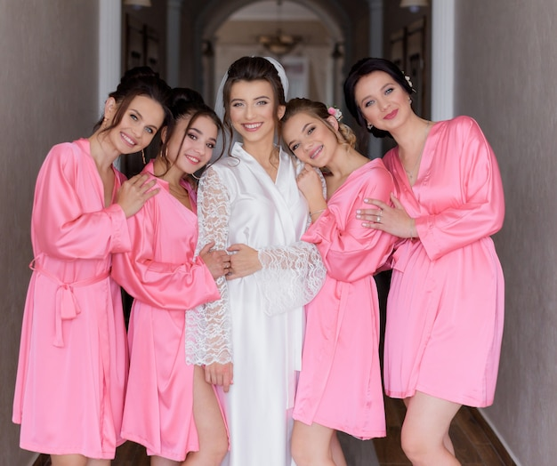 Smiled happy bridesmaids dressed in pink silky nightwear with beautiful bride in the hall
