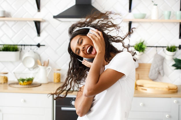 Smiled hilarious mulatto woman with messy hair in big wireless headphones is happily dancing with her opened mouth in the modern kitchen