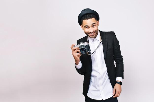 スーツ、帽子で笑顔のうれしそうな若い男。ファッショナブルな外観、モダン、カメラ付き観光客、旅行、楽しんで、肯定的な感情を表現します。