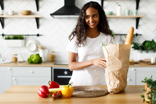 Smiled mulatto woman is holding package with baguette and vegetables on the modern white kitchen